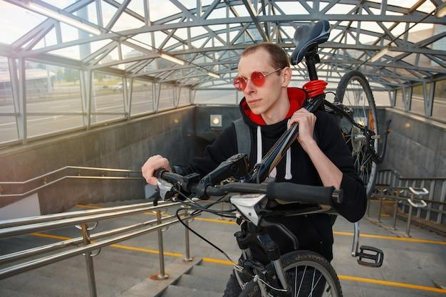 若いバイカーが地下道の階段を上り、自転車を肩に乗せている
