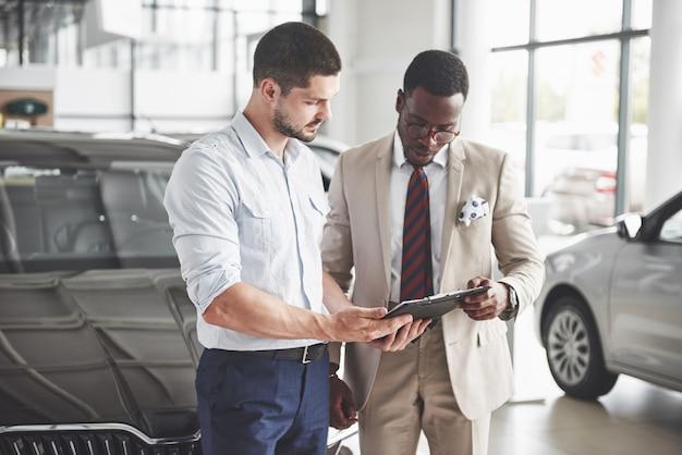 젊은 흑인 사업가 문서에 서명하고 새 차를 구입합니다. 자동차 딜러가 그 옆에 서 있습니다