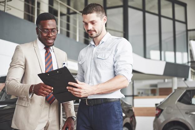 Молодой темнокожий бизнесмен подписывает документы и покупает новую машину. рядом с ним стоит автосалон.