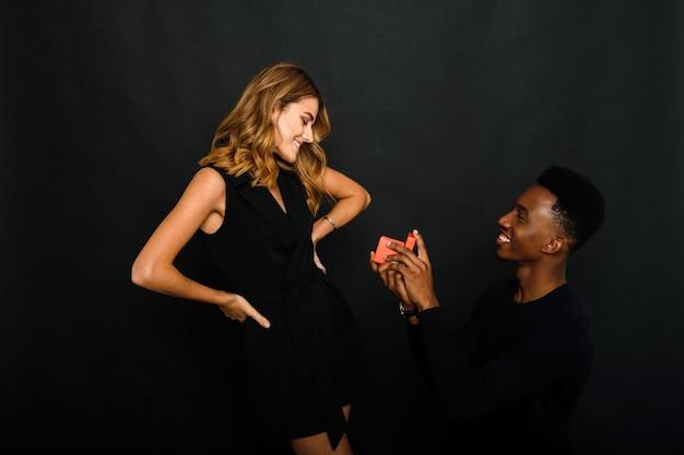 Молодой темнокожий мужчина делает подарок своей кавказской девушке и делает ей предложение, стоя на одном колене.