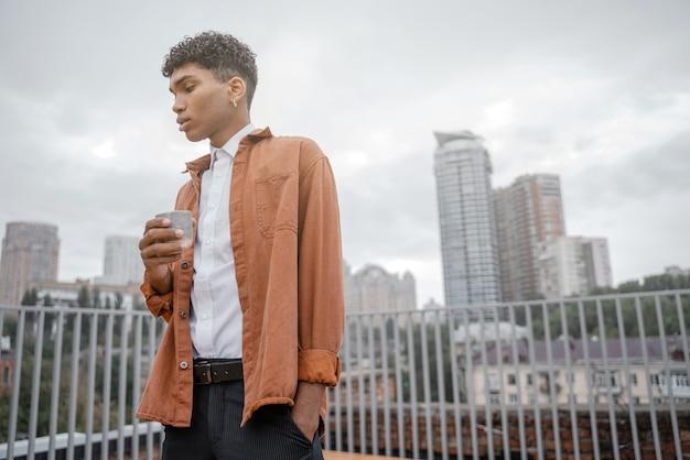 갈색 재킷을 입은 한 젊은 흑인 남성이 도시의 스카이라인이나 시내를 배경으로 손에 컵에 담긴 음료를 들고 있습니다. 그 남자는 도시 배경에서 커피나 차를 마신다.