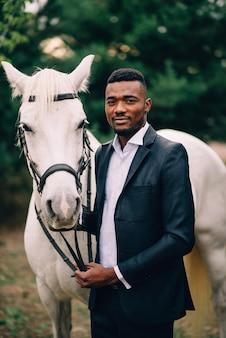 古典的な黒いスーツを着た若い黒人男性が白い馬の手綱を握っています