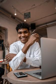 若い黒人男性がノートパソコンを持ってテーブルに座って、お茶を飲み、スマートフォンを使用しています。カフェの男。オフィスの外での作業、リモートワークまたは学習コンセプト。縦の写真。