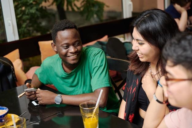 Молодой темнокожий мужчина рассказывает анекдот своей девушке в окружении друзей в современном кафе.