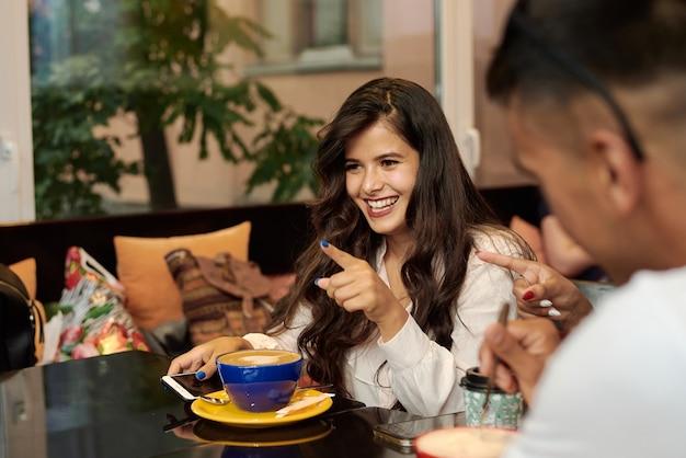 Молодая темнокожая женщина смеется, разговаривает со своими друзьями и пьет кофе.