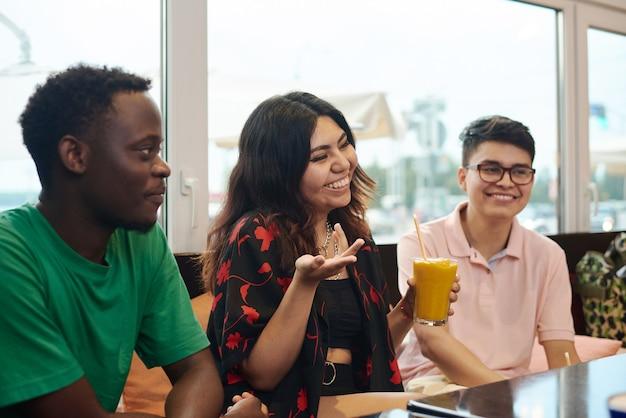 Молодая темнокожая женщина смеется, разговаривая со своими друзьями-мужчинами.