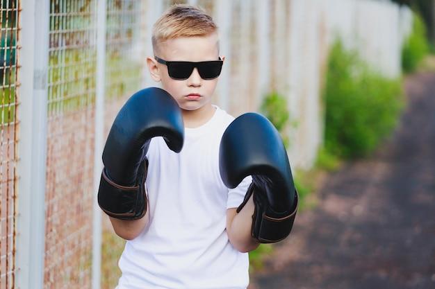 Молодой белокурый мальчик в белой футболке и солнечных очках держит руки у головы в боксерских перчатках. фото высокого качества