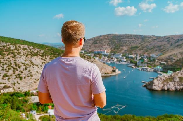 Молодой блондин наслаждается живописным пейзажем с видом на балаклаву с яхтами.