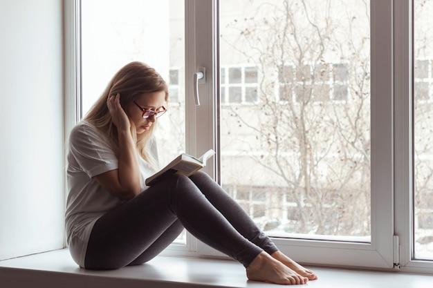 白いtシャツと眼鏡をかけた灰色のレギンスを着た若い金髪の美しい女性が窓辺に座って本を読んでいます。