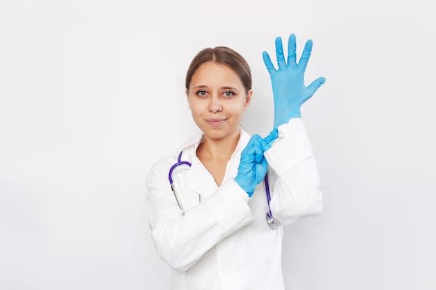 若い金髪の女性の笑顔の医者は、患者を診察する前に青い医療用手袋を着用します