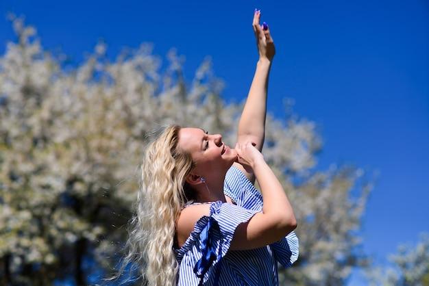 若いブロンドの女の子は、美しい青い空を見て、彼女の手で空に手を伸ばします。美しい女性は自然を賞賛します。