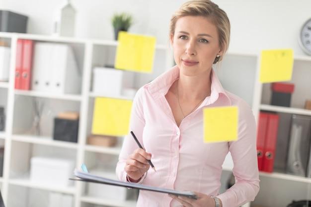 若いブロンドの女の子は、ステッカーの付いた透明なボードの隣のオフィスに立ち、ドキュメントと鉛筆を手に持っています。