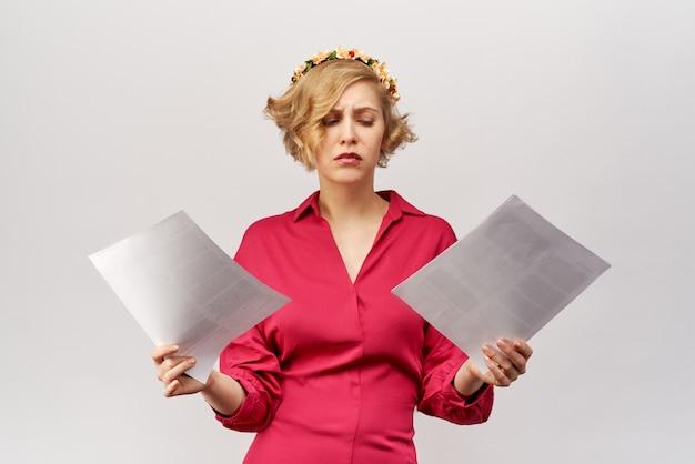 Молодая блондинка с потерянным взглядом смотрит на документы, раскинувшие руки перед собой в замешательстве и недоразумении.