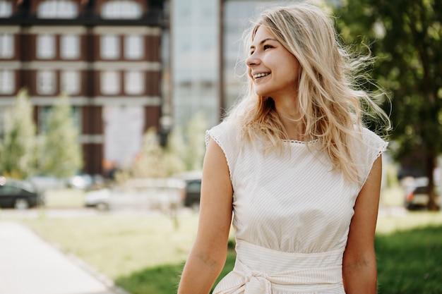 Молодая блондинка в белом платье на фоне европейского города. концепция образа жизни и счастья