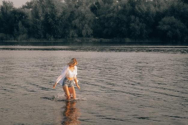 若いブロンドが夜明けに水の中を走っています。白いトップス、シャツ、デニムのショートパンツを着た若い女性が水を見て、美しい風景を背景に川に沿って走っています。