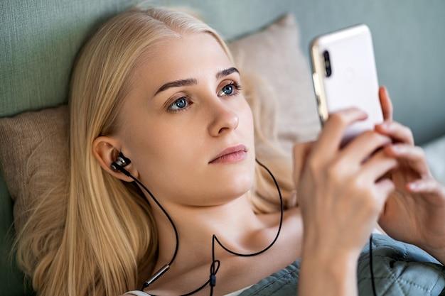 젊은 금발은 녹색 담요 아래 그녀의 침대에 놓여 있습니다. 그녀는 헤드폰이 연결된 전화기를 들고 있습니다. 소녀는들을 노래를 선택합니다. 그녀는 밝은 파란 눈을 가지고