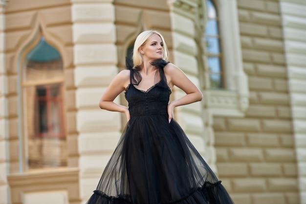 Молодая блондинка стоит возле старого дома в черном платье