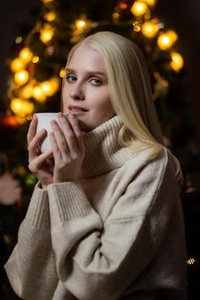 젊은 금발의 여자는 크리스마스 트리 근처 집에서 향기로운 코코아를 마신다.
