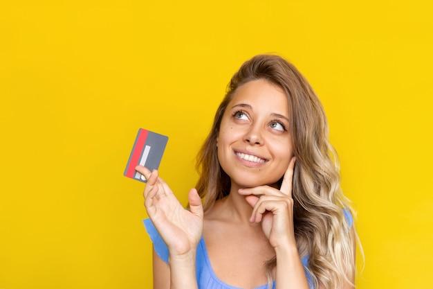 플라스틱 신용 카드를 손에 들고 돈을 쓰는 방법에 대해 생각하는 젊은 금발 여성