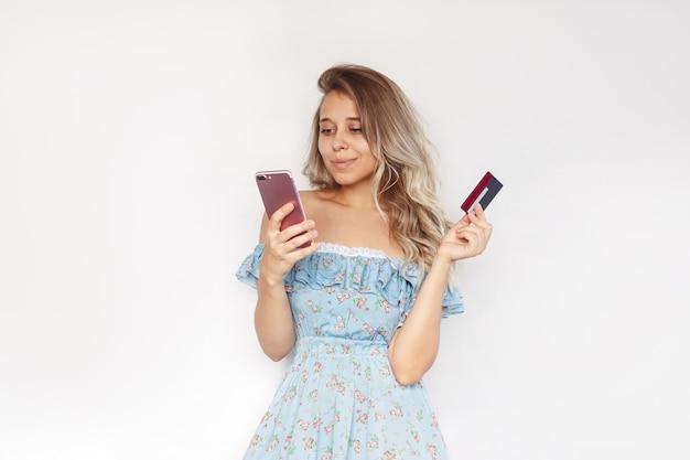 若いブロンドの女性がオンライン購入をしている携帯電話の画面を見ているクレジットカードを持っています