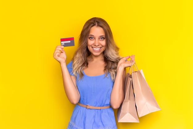 한 젊은 금발 여성이 손에 종이 에코백을 들고 플라스틱 신용카드를 보여주고 있다