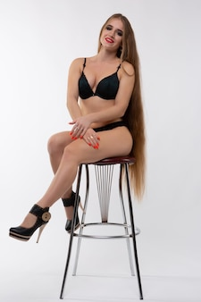 На стуле сидит молодая блондинка в бикини.