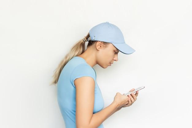 허리를 굽힌 파란색 모자를 쓴 젊은 금발 여성이 휴대폰 화면 곡률을 바라보고 있다
