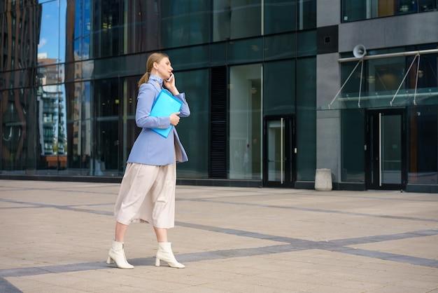 Молодая блондинка в классическом пиджаке и юбке разговаривает по телефону и держит документы на фоне бизнес-центра. концепция работы.