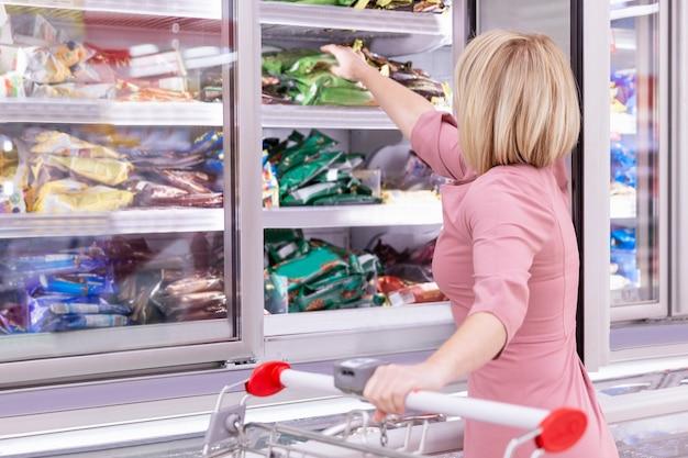 냉동 식품 부서의 식료품 점에서 젊은 금발의 여자가 제품을 선택