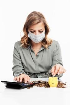 의료 마스크에 젊은 금발의 여자는 수입을 계산하고 있습니다.