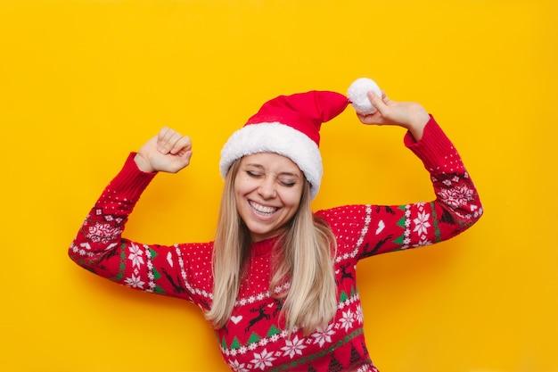 赤い鹿の暖かいセーターとサンタクロースの帽子をかぶった若いブロンドの女性は彼女の手を上げて満足しています