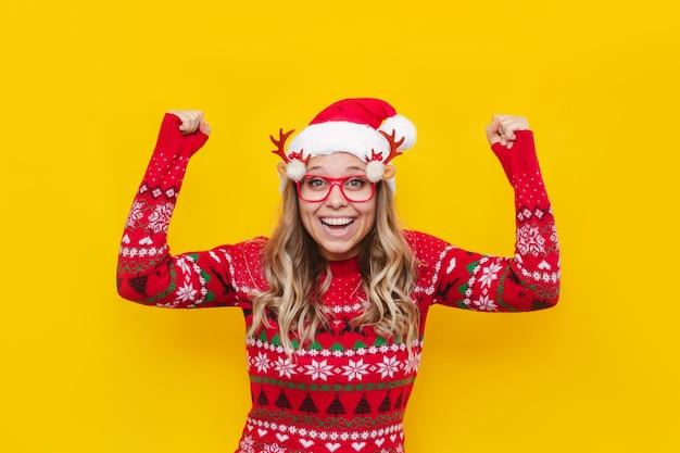 クリスマスのサンタの帽子と赤い鹿のセーターの若いブロンドの女性は彼女の手を上げて満足しています