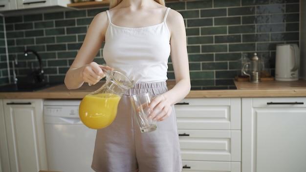 Молодая блондинка наливает апельсиновый сок в стакан и пьет. довольно стройная женщина пьет сочный апельсиновый сок на кухне. камера движется снизу вверх, 4k uhd.