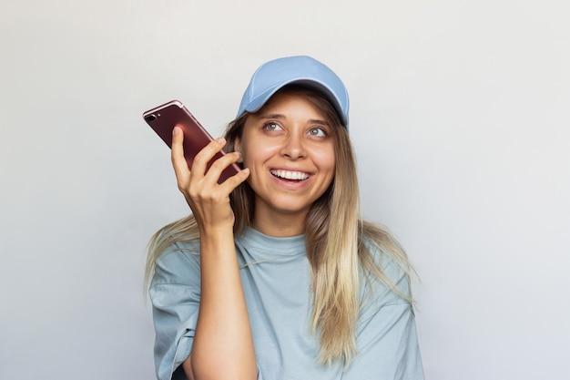 若いブロンドの女性は微笑んで、音声メッセージを聞いている彼女の耳の近くに携帯電話を持っています