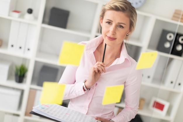 若いブロンドの女性は、ステッカーが貼られた透明なボードの隣のオフィスに立ち、ドキュメントと鉛筆を手に持っています。
