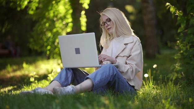 노트북을 들고 있는 젊은 금발 여성이 공원의 푸른 초원에 앉아 있습니다. 즐거움, 원격 근무, 창의성을 위해 일하십시오. 4k uhd