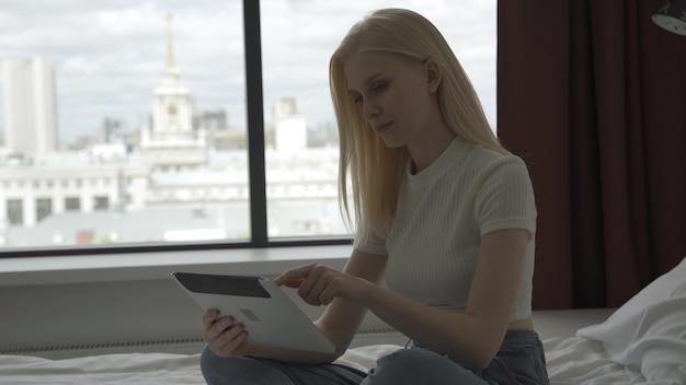 若いブロンドの女性は、大きな窓の近くの窓辺でラップトップの後ろで働いています。美しい女性がラップトップを開き、キーボードで入力を開始します。フリーランスとリモートワークのコンセプト。 4k uhd