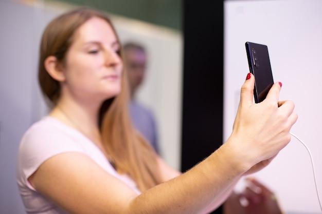 若いブロンディの女性が手に持っている黒いスマートフォンが自分撮りをしてそれを調べますc
