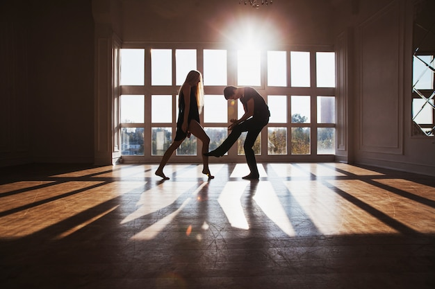 少年と窓の前に立っている長いブロンドの髪を持つ少女。ワークアウト中のダンサー。関係の問題と困難。人生の困難な状況。概念的な写真