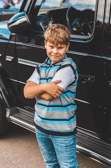 줄무늬 스웨터를 입은 어린 소년이 차 옆에 서 있다