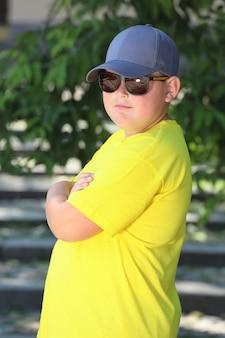 黄色いtシャツと帽子とサングラスを着た少年が自然の中に立っています。高品質の写真