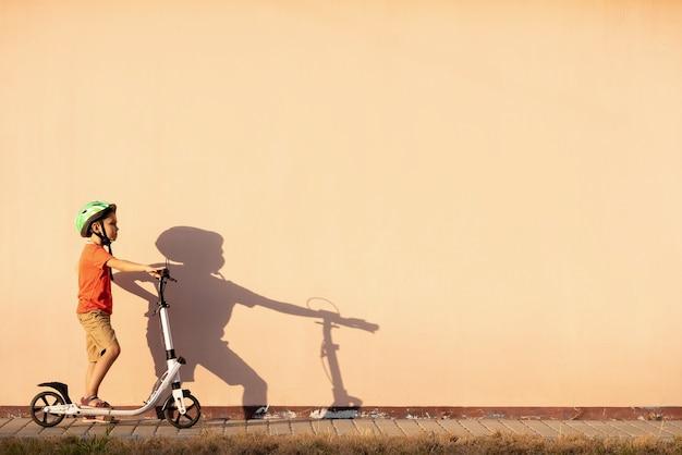 少年は保護ヘルメットでスクーターに乗っています