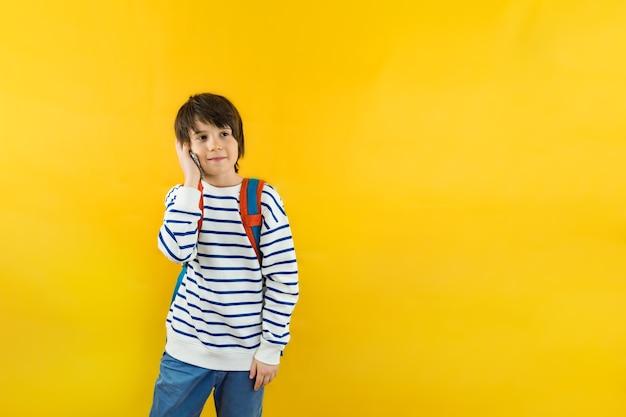 그의 어깨에 배낭이있는 9 세의 어린 소년이 부모 또는 친구와 스마트 폰으로 이야기합니다.