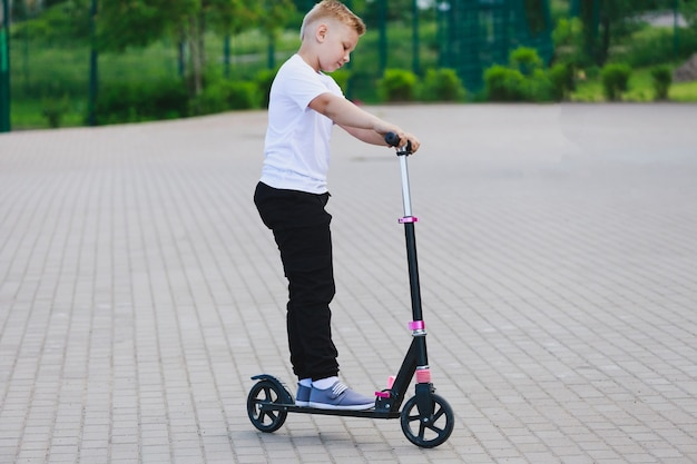 少年は公園で夏にスクーターに乗る。高品質の写真