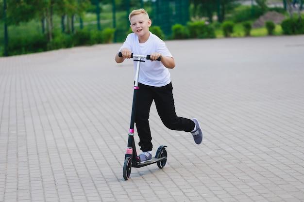 夏にスクーターに乗る少年。高品質の写真