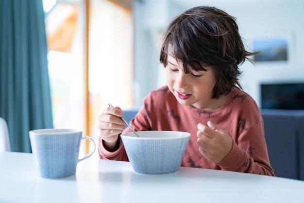 잠옷을 입은 어린 소년이 학교 시작 전 아침에 집에서 아침을 먹고 있습니다. 어린이를 위한 건강식.