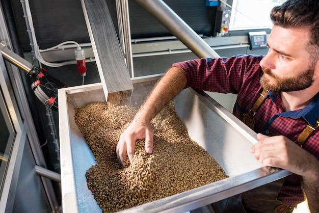 革のエプロンを着た若い醸造所が、現代の醸造所の製粉所で麦芽種子の粉砕を管理しています