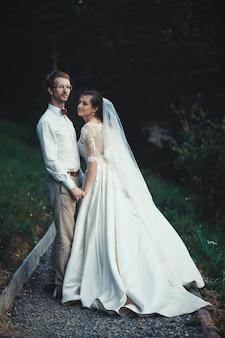 Молодая невеста и жених, стоя вместе на открытом воздухе, летнее время
