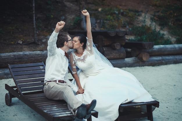 Молодая невеста и жених, стоя вместе на открытом воздухе