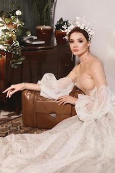 Молодая невеста со стильной свадебной прической с цветочным декором в модном свадебном платье ...